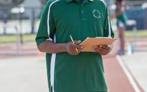 Athletics coach holding a pen and clipboard