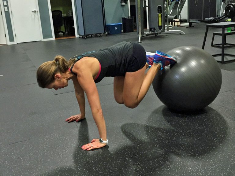 A woman performing ab exercises with a swiss ball