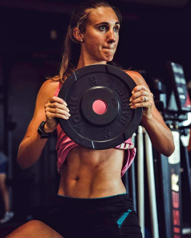 Athlete working her abs with a weight plate
